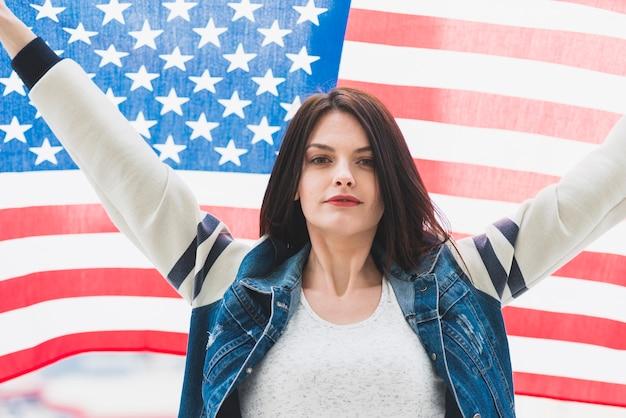 Amerikanische flagge und frau mit den händen oben