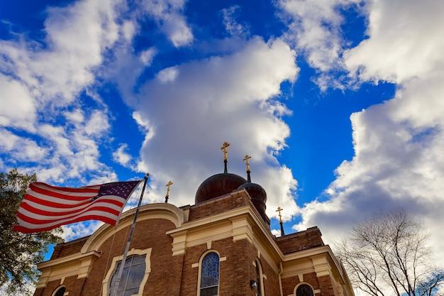Amerikanische flagge und religiöses kreuz bei sonnenuntergang american flag church