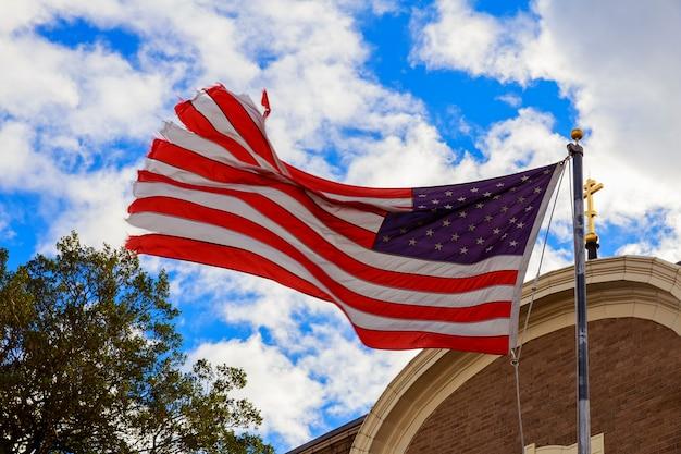 Amerikanische flagge und religiöses kreuz bei sonnenuntergang