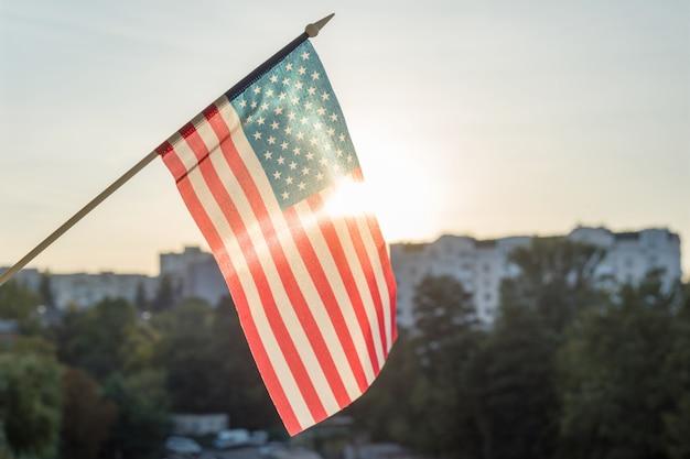 Amerikanische flagge vom fenster, auf sonnenunterganghintergrund