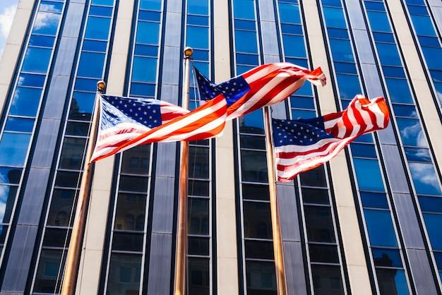 Amerikanische flaggen, die auf glasigen gebäudehintergrund wellenartig bewegen