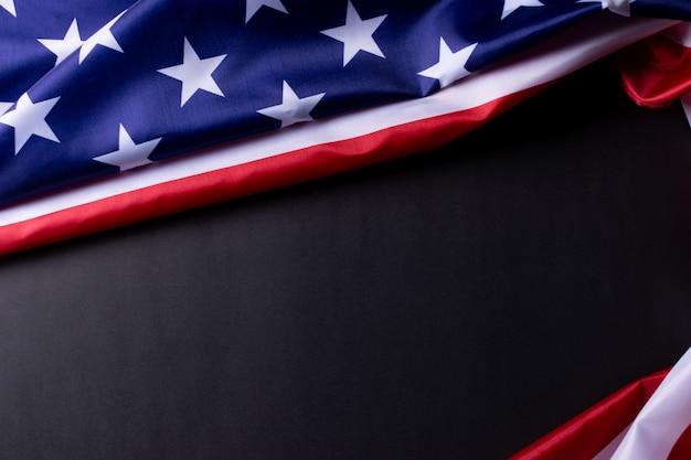 Amerikanische flaggen gegen einen schwarzen papierhintergrund