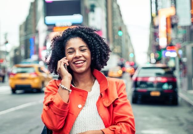 Amerikanische frau, die einen anruf in time square, new york macht. urbanes lifestyle-konzept