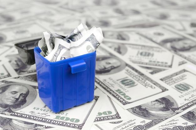 Amerikanische geldscheine werden auf hunderten von dollarnoten in den mülleimer geworfen