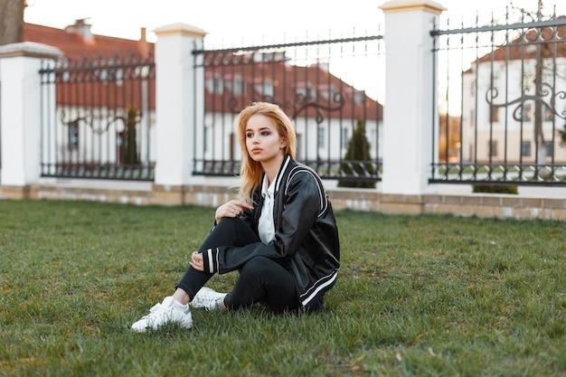 Amerikanische junge attraktive frau in einer stilvollen jacke in schwarzen jeans in weißen turnschuhen sitzt auf einem grünen rasen eines weißen weinlesegebäudes bei sonnenuntergang. süßes mädchen.