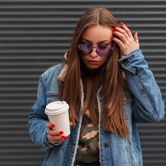 Amerikanische junge hipster-frau in stilvoller, glamouröser lila brille in trendiger blauer jeansjacke mit kaffee glättet das haar und schaut in der nähe der vintage-metallwand nach unten. nettes mädchen-mode-modell im freien.