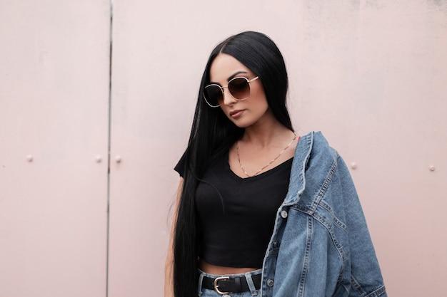 Amerikanische junge hipster-frau in stilvoller sonnenbrille in einem schwarzen oberteil in einer modischen blauen jeansjacke in einem trendigen rock steht nahe einer wand in der stadt im freien. ziemlich attraktives mädchenmodel.