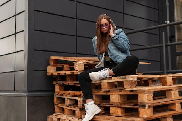 Amerikanische junge hübsche coole hipster-frau in stylischer jeanskleidung in modischer lila brille in weißen lederstiefeln ruht auf holzpaletten in der nähe der wand in der stadt. attraktives mädchen. legerer stil