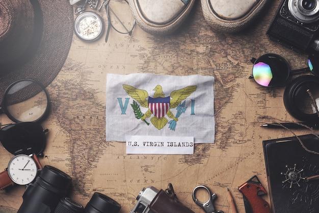 Amerikanische jungferninseln-flagge zwischen dem zubehör des reisenden auf alter weinlese-karte. obenliegender schuss
