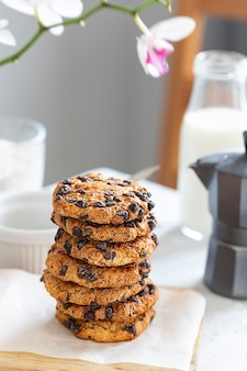 Amerikanische kekse mit schokoladenstückchen werden auf einem holzbrett ausgelegt