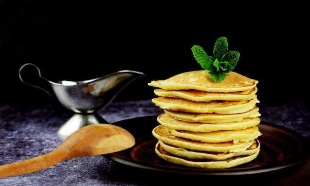Amerikanische pfannkuchen auf einer platte mit honig und minze
