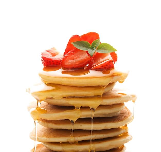 Amerikanische pfannkuchen mit erdbeeren und honig isoliert
