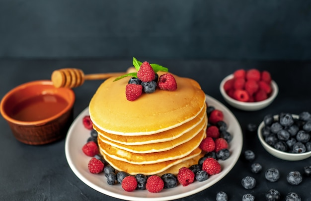 Amerikanische pfannkuchen mit himbeeren, frischen blaubeeren und honig. gesundes frühstück auf beton