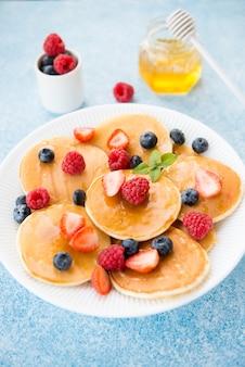 Amerikanische pfannkuchen zum frühstück mit honig und beeren