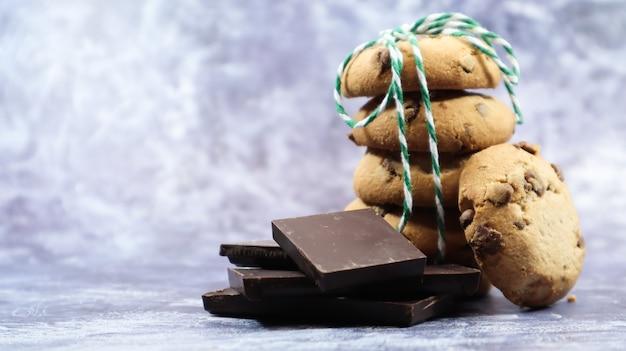 Amerikanische schokoladenkekse, die auf einem schönen grauen marmorhintergrund übereinander gestapelt sind. traditioneller abgerundeter knuspriger teig mit schokoladenstückchen. leckeres dessert, gebäck. platz kopieren.