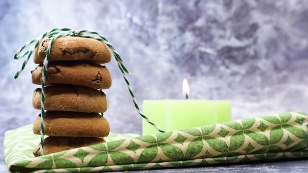Amerikanische schokoladenkekse in einem stapel, der mit faden auf einer grünen serviette und einer kerze gebunden ist. traditioneller abgerundeter knuspriger teig mit schokoladenstückchen. bäckerei. leckeres dessert, gebäck.