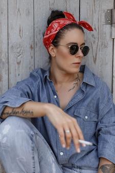 Amerikanische stilvolle frau mit einem kopftuch und einer sonnenbrille in modischer denim-kleidung, die eine zigarette nahe einer holzwand raucht