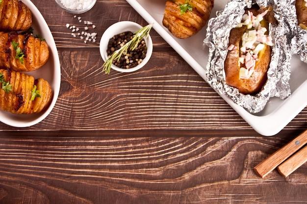 Amerikanische traditionelle hausgemachte hasselback-kartoffel und gefüllte kartoffeln mit frischen kräutern und speck. ansicht von oben. platz kopieren.