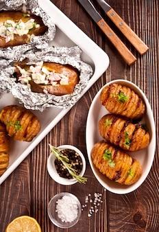 Amerikanische traditionelle hausgemachte hasselback-kartoffel und gefüllte kartoffeln mit frischen kräutern und speck. ansicht von oben.