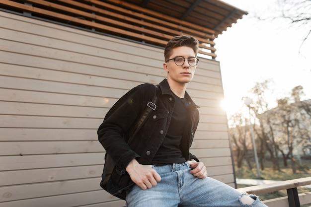 Amerikanischer cooler junger mann in trendiger, lässiger denim-kleidung in stilvoller brille mit trendigem schwarzem rucksack genießt entspannung und sonnenstrahlen in der nähe der holzwand im freien