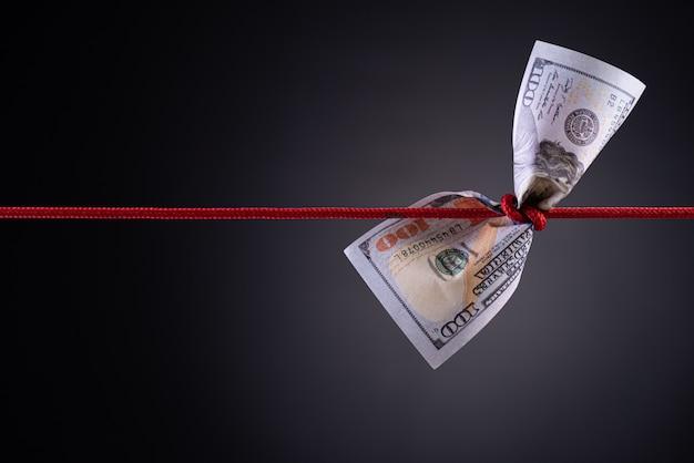 Amerikanischer dollar oben gebunden im roten seilknoten auf dunkelheit mit kopienraum