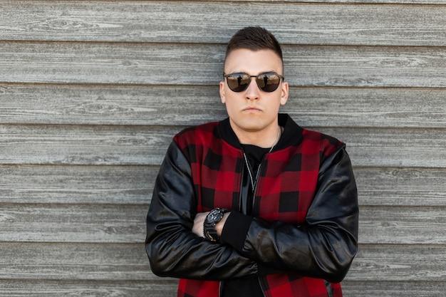 Amerikanischer ernsthafter junger hipster-mann in der schwarzen sonnenbrille in einer vintage rot karierten jacke in einem schwarzen t-shirt mit einer stilvollen frisur nahe einer holzwand im freien