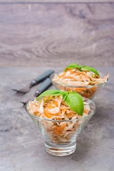 Amerikanischer essfertiger krautsalatsalat des kohls, des selleries, der karotten und der äpfel mit basilikum verlässt in den glasschüsseln auf dem tisch.