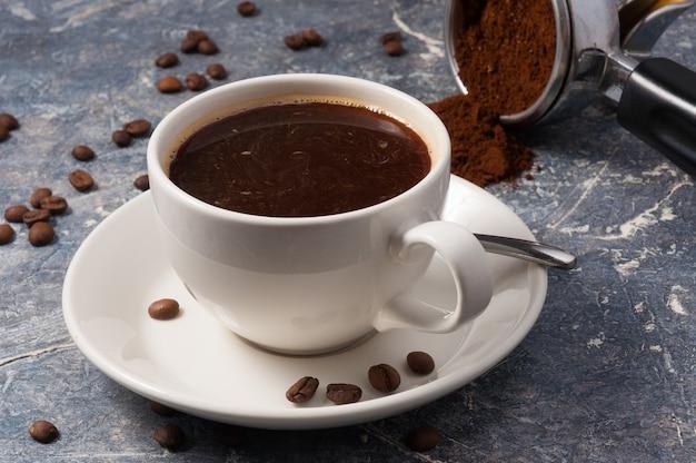 Amerikanischer filter des heißen kaffees auf einem grauen hintergrund, der mit kaffeebohnen verziert wird