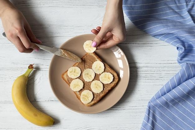 Amerikanischer frühstücks-weißbrot-toast mit erdnussbutter und bananenscheiben