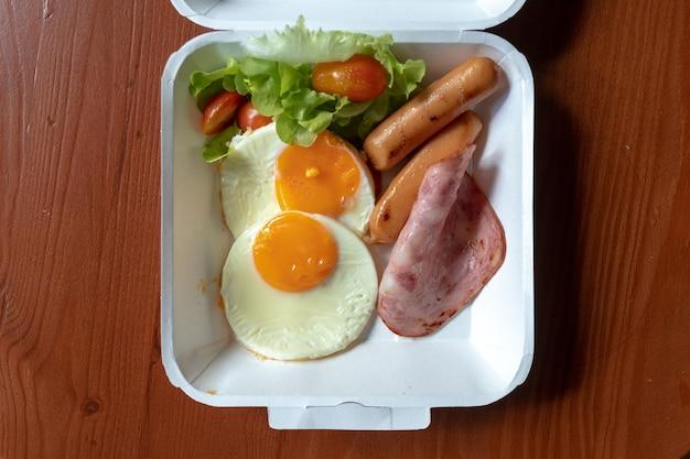 Amerikanischer frühstücksmahlzeitstil in einem papierkastensatz. kleine mahlzeit aus schinken und spiegeleiern.