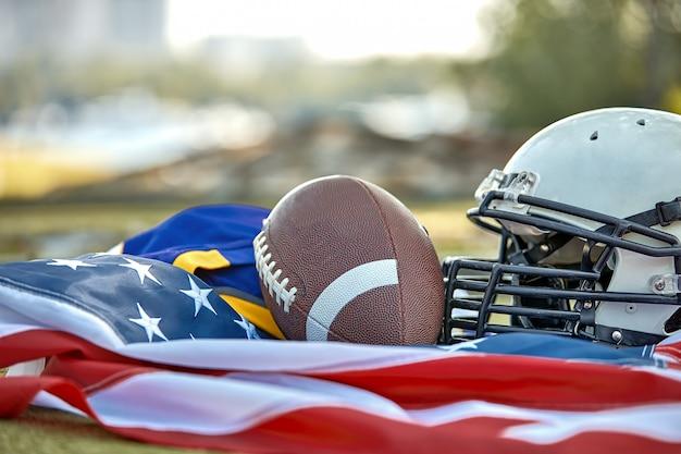 Amerikanischer fußball. ausrüstung des amerikanischen fußballs, sturzhelm, ballnahaufnahme auf der amerikanischen flagge. patriotismus.