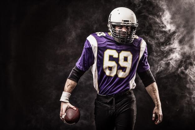 Amerikanischer fußballspieler, der ball in seinen händen im rauch hält. schwarzer raum, kopierraum. das konzept des american football, motivation, kopierraum