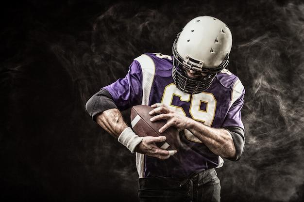 Amerikanischer fußballspieler, der ball in seinen händen im rauch hält
