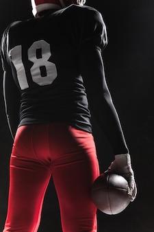 Amerikanischer fußballspieler, der mit ball auf schwarzem hintergrund aufwirft