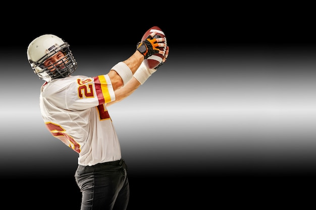 Amerikanischer fußballspieler in bewegung mit dem ball auf einem schwarzen hintergrund mit einer hellen linie, kopienraum. konzept des spiels ist american football, bewegung.