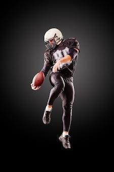 Amerikanischer fußballspieler in einem sprung mit einem ball auf einem schwarzen hintergrund