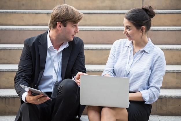 Amerikanischer geschäftsmann und geschäftsfrau sitzen und besprechen geschäftsplan in der stadt durch firmenlaptopcomputer. teamwork-meeting außerhalb des büros.