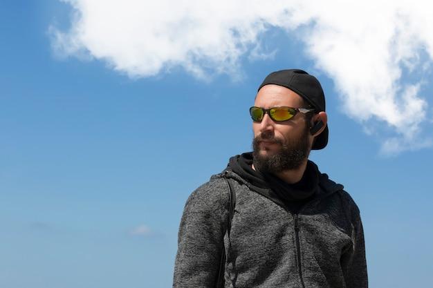 Amerikanischer gutaussehender bärtiger mann mit sonnenbrille, mütze und kapuzenjacke gegen blauen himmel mit wolken. porträt des russisch-kaukasischen brutalen typen sieht zur seite, entspannte pose mit natürlichem gesicht. platz kopieren