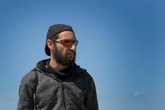 Amerikanischer gutaussehender bärtiger mann mit sonnenbrille, mütze und kapuzenjacke gegen blauen himmel. porträt des russisch-kaukasischen brutalen typen sieht zur seite, entspannte pose mit natürlichem gesicht. platz kopieren. mode mann