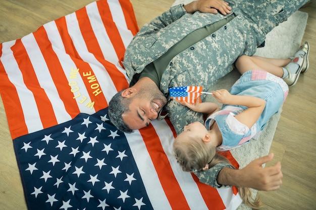 Amerikanischer held. blondes süßes mädchen, das sich wirklich glücklich fühlt, während sie ihren amerikanischen helden zu hause trifft