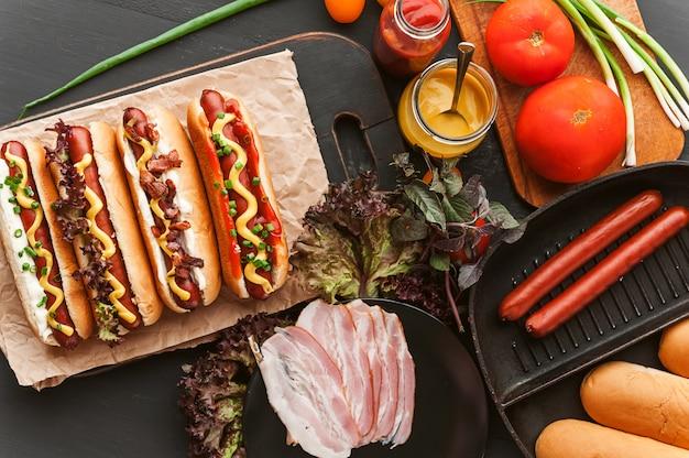 Amerikanischer hotdog mit bestandteilen auf einem dunklen hölzernen hintergrund