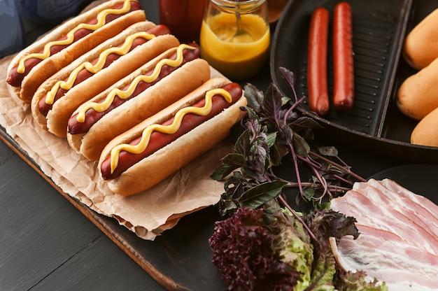 Amerikanischer hotdog mit bestandteilen auf einer dunklen holzoberfläche