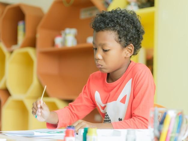 Amerikanischer junge, der haus trägt, trug zeichnungsfarbbleistifte im kindergartenklassenzimmer