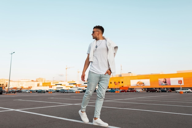 Amerikanischer junger mann in sonnenbrille in vintage blue jeans in einem stilvollen weißen t-shirt in turnschuhen geht durch die stadt. urbaner typ, der auf der straße geht. sommerjugendmode. modische herrenmode