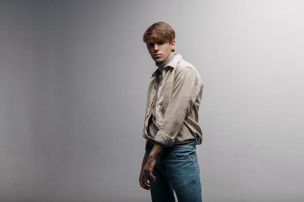 Amerikanischer junger mann mit einer modischen frisur in einer leichten, leichten, stilvollen jacke im retro-stil in blauen vintage-hosen steht im studio nahe einer weißen wand. netter kerl. moderner jugendstil