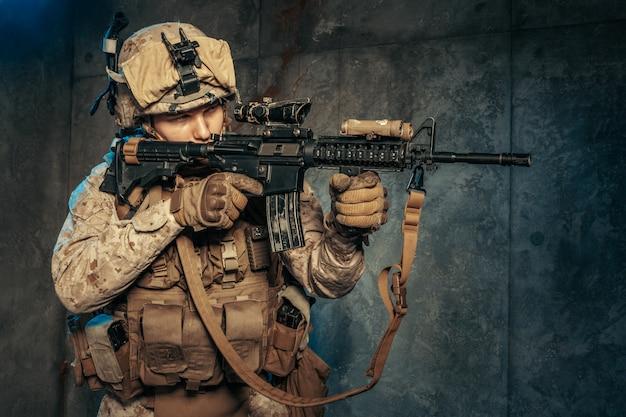 Amerikanischer privater militärunternehmer, der ein gewehr schießt. studioaufnahme