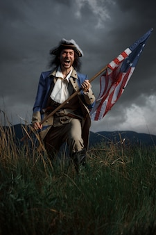 Amerikanischer revolutionskriegssoldat mit flagge der kolonien über dramatischer landschaft
