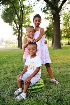 Amerikanischer schwarzafrikaner scherzt das spielen mit einer großen wassermelone im park auf dem gras und dem lächeln.
