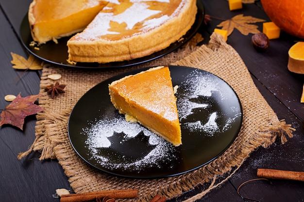 Amerikanischer selbst gemachter kürbiskuchen mit zimt und muskatnuss, kürbiskernen und herbstlaub auf einem holztisch. thanksgiving-essen.