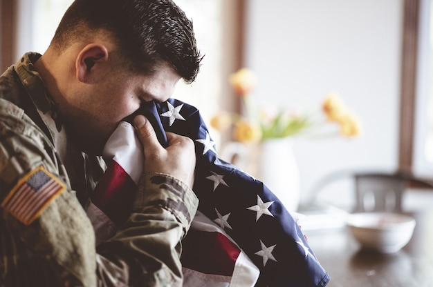 Amerikanischer soldat, der mit der amerikanischen flagge in seinen händen trauert und betet